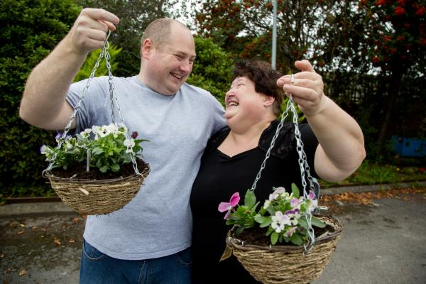 Dot and her son holding hanging baskets