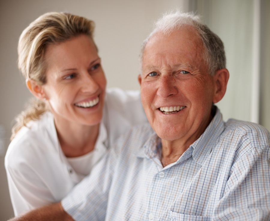 A man and his carer laughing together